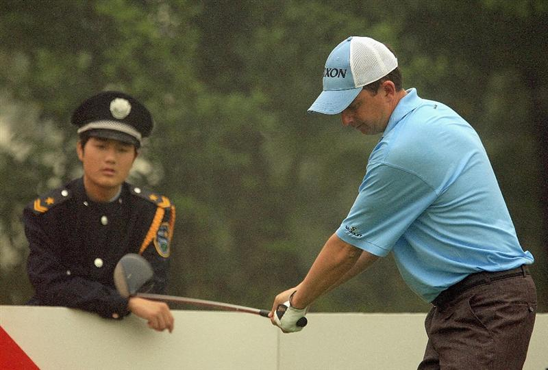 SHANGHAI, CHINA - NOVEMBER 06:  Peter Lawrie of Ireland waits on the ninth tee as a Chinese guard looks on during the first round of the HSBC Champions at Sheshan International Golf Club on November 6, 2008 in Shanghai, China.  (Photo by Scott Halleran/Getty Images)