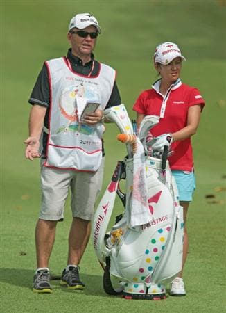 SINGAPORE - FEBRUARY 26:  Caddy of the Year Mick Seaborn alongside player Ai Miyazato of Japan during the third round of the HSBC Women's Champions 2011 at the Tanah Merah Country Club on February 26, 2011 in Singapore, Singapore.  (Photo by Scott Halleran/Getty Images)