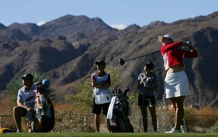 PALM DESERT, CA - OCTOBER 13:  Angela Park makes a tee shot on the fourth hole as Paula Creamer, Creamer's caddie Colin Cann and Park's caddie Mike Hobbs look on during the third round of the LPGA Samsung World Championship at the Bighorn Golf Club on October 13, 2007 in Palm Desert, California.  (Photo by Robert Laberge/Getty Images)