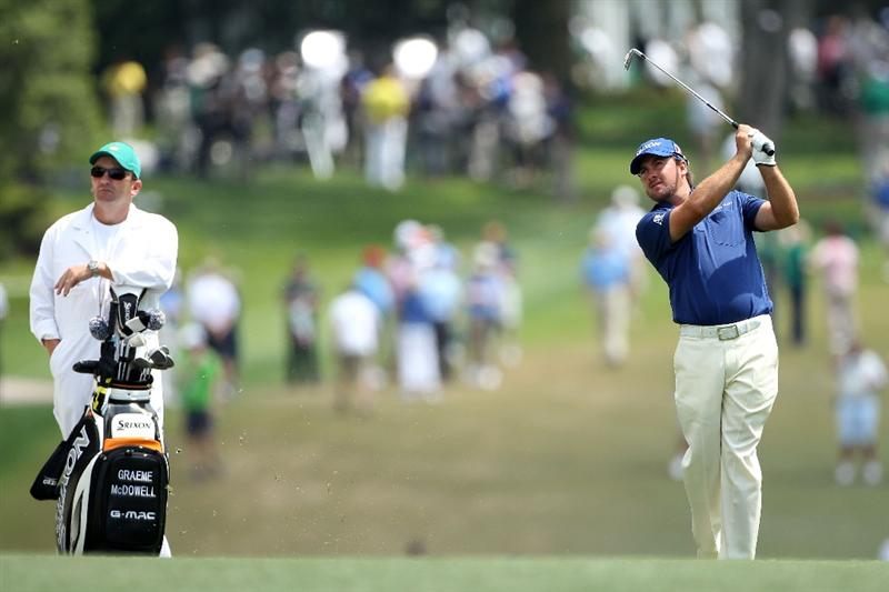 AUGUSTA, GA - APRIL 08:  Graeme McDowell of Northern Ireland hits a shot on the first hole as his caddie Ken Comboy looks on during the second round of the 2011 Masters Tournament at Augusta National Golf Club on April 8, 2011 in Augusta, Georgia.  (Photo by Andrew Redington/Getty Images)