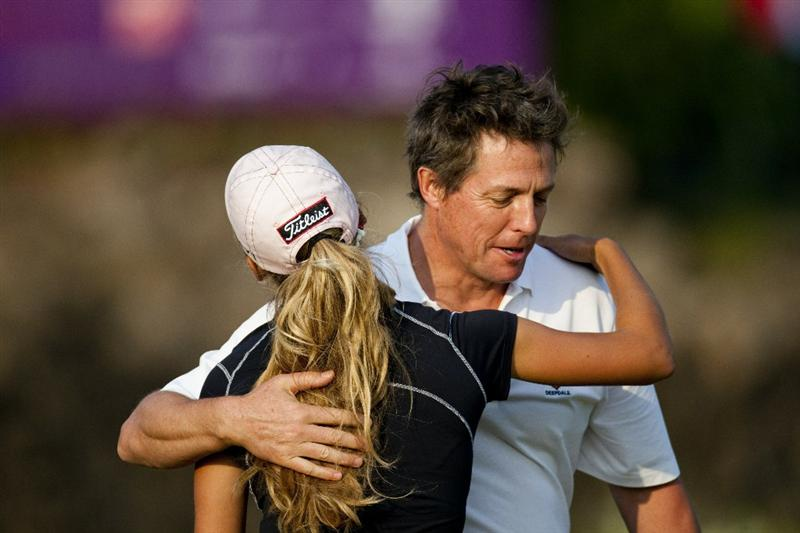 HAIKOU, CHINA - OCTOBER 30:  Hollywood actor Hugh Grant of Great Britain hugs with golfer Belen Mozo of Spain during day four of the Mission Hills Start Trophy tournament at Mission Hills Resort on October 30, 2010 in Haikou, China. The Mission Hills Star Trophy is Asia's leading leisure liflestyle event which features Hollywood celebrities and international golf stars.  (Photo by Athit Perawongmetha/Getty Images for Mission Hills)