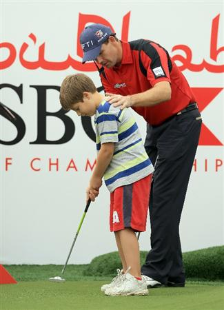 ABU DHABI, UNITED ARAB EMIRATES - JANUARY 22:  Padraig Harrington of Ireland offers advice to a young golfer at a skills clinic during the third round of The Abu Dhabi HSBC Golf Championship at Abu Dhabi Golf Club on January 22, 2011 in Abu Dhabi, United Arab Emirates.  (Photo by Andrew Redington/Getty Images)