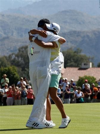 RANCHO MIRAGE, CA - APRIL 04:  Yani Tseng of Taiwan embraces her caddie Dave Poitevent after holing the winning putt on the 18th green during the final round of the 2010 Kraft Nabisco Championship, on the Dinah Shore Course at The Mission Hills Country Club, on April 4, 2010 in Rancho Mirage, California.  (Photo by David Cannon/Getty Images)