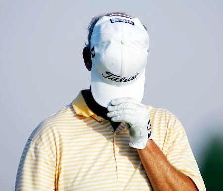Scotland's Sandy Lyle hides from photographers as a joke during the second round of the Dubai Desert Classic at the Emirates Golf Club in Dubai on March 3, 2005