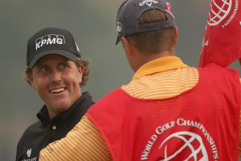 SHANGHAI, CHINA - NOVEMBER 08:  Phil Mickelson of the USA smiles to his caddie Jim MacKay on the 18th green during the final round of the WGC-HSBC Champions at Sheshan International Golf Club on November 8, 2009 in Shanghai, China.  (Photo by Andrew Redington/Getty Images)