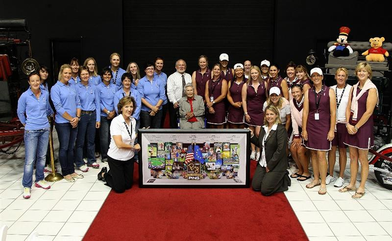SUGAR GROVE, IL - AUGUST 17:  Members of the European and U.S. Solheim teams along with Marty Evans of the LPGA and Alexandra Armas of the Ladies European Tour present the Solheim family with a framed artwork inside the car museum on the grounds of Rich Harvest Farms, host site of the 2009 Solheim Cup on August 17, 2009 in Sugar Grove, Illinois.  (Photo by David Cannon/Getty Images)