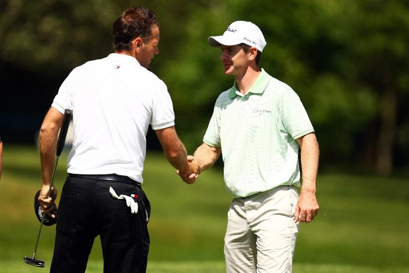 WENTWORTH, ENGLAND - MAY 21: Nick Dougherty (L) of England and Scott Strange of Australia shake hands on the 18th green after the First Round of the BMW PGA Championship at Wentworth on May 21, 2009 in Virginia Water, England.  (Photo by Ian Walton/Getty Images)