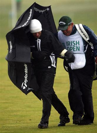 BALTRAY, IRELAND - MAY 16:  Steve Webster of England (left) and his caddoe Dave McNeilly struggle in the high winds and rain on the 11th hole during the third round of The 3 Irish Open at County Louth Golf Club on May 16, 2009 in Baltray, Ireland.  (Photo by Andrew Redington/Getty Images)