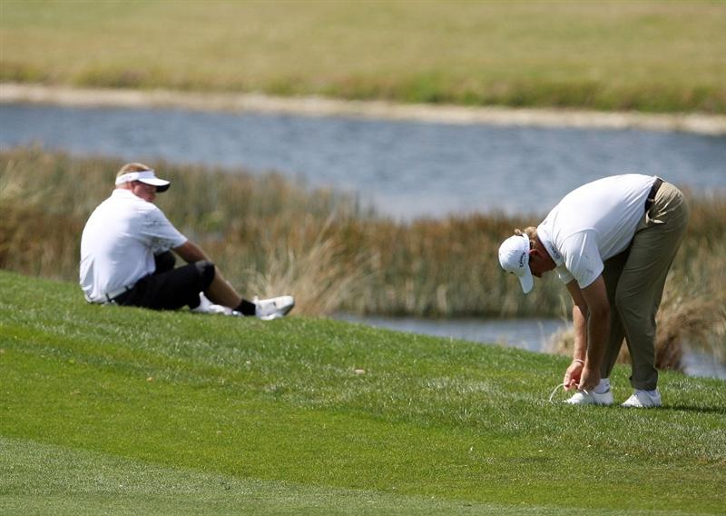 PALM BEACH GARDENS, FL - MARCH 05: Carl Pettersson, L, and Ernie Els wipe mud off their feet after both had to hit out of the water hazard on the sixth fairway during the first round of The Honda Classic at PGA National Resort and Spa on March 5, 2009 in Palm Beach Gardens, Florida.  (Photo by Doug Benc/Getty Images)