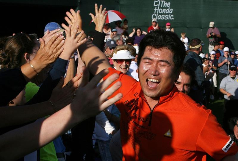 PALM BEACH GARDENS, FL - MARCH 08:  Y.E.Yang celebrates by high-fiving the crowd after winning The Honda Classic at PGA National Resort and Spa on March 8, 2009 in Palm Beach Gardens, Florida.  (Photo by Doug Benc/Getty Images)