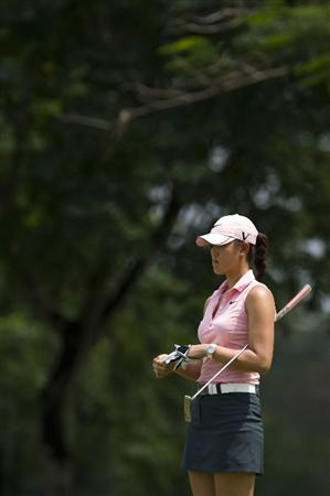 CHON BURI, THAILAND - FEBRUARY 20:  Michelle Wie of USA removes her glove on the 2nd green during round three of the Honda PTT LPGA Thailand at Siam Country Club on February 20, 2010 in Chon Buri, Thailand.  (Photo by Victor Fraile/Getty Images)