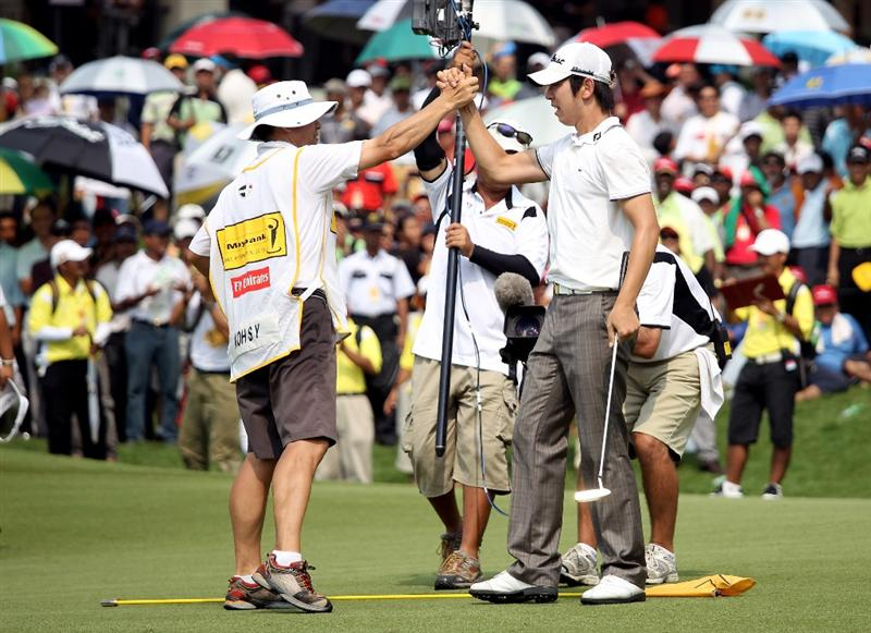 KUALA LUMPUR, MALAYSIA - MARCH 07:  Noh Seung-yul of Korea celebrates with his caddie on the 18th green after winning the Maybank Malaysia Open at the Kuala Lumpur Golf & Country on March 7, 2010 in Kuala Lumpur, Malaysia.  (Photo by Ross Kinnaird/Getty Images)