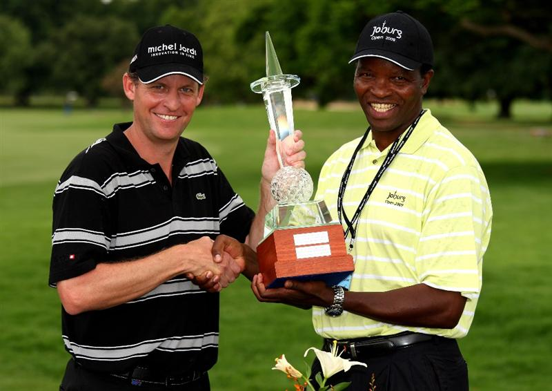JOHANNESBURG, SOUTH AFRICA - JANUARY 11:  Anders Hansen of Denmark is presented with the trophy by the Johannesburg City Manager Mavela Dlamini after securing a one shot victory in the final round of the Joburg Open at Royal Johannesburg and Kensington Golf Club on January 11, 2009 in Johannesburg, South Africa.  (Photo by Richard Heathcote/Getty Images)