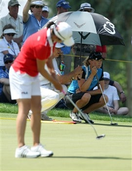 RANCHO MIRAGE, CA - APRIL 5:  Annika Sorenstam (R) of Sweden shelters from the sun at the first green as her playing partner Hee-Won Han of South Korea putts during the third round of the Kraft Nabisco Championship at the Mission Hills Country Club April 5, 2008 in Rancho Mirage, California.  (Photo by David Cannon/Getty Images)