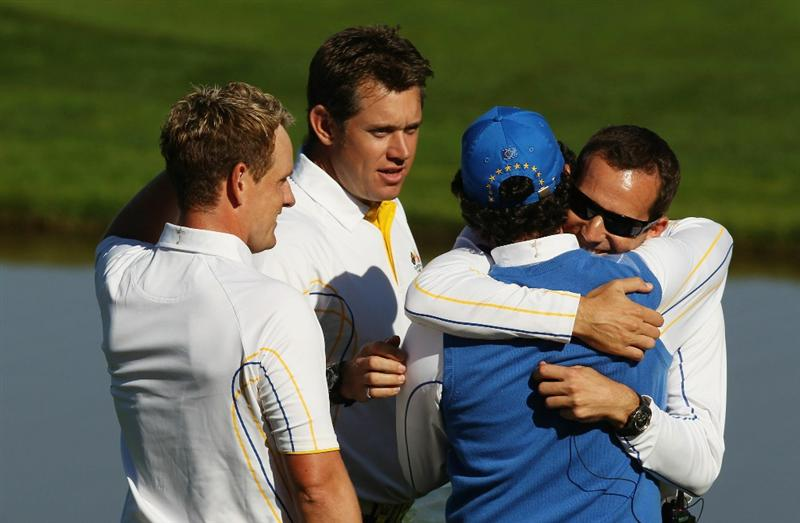 NEWPORT, WALES - OCTOBER 04:  Rory McIlroy of Europe embraces Vice Captain Sergio Garcia on the 18th green after he halved his match in the singles matches during the 2010 Ryder Cup at the Celtic Manor Resort on October 4, 2010 in Newport, Wales.  (Photo by Ross Kinnaird/Getty Images)