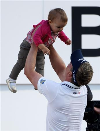VIRGINIA WATER, ENGLAND - MAY 29:  Luke Donald of England lifts up his daughter Elle following his victory in a playoff on the 18th green during the final round of the BMW PGA Championship  at the Wentworth Club on May 29, 2011 in Virginia Water, England.  (Photo by Warren Little/Getty Images)