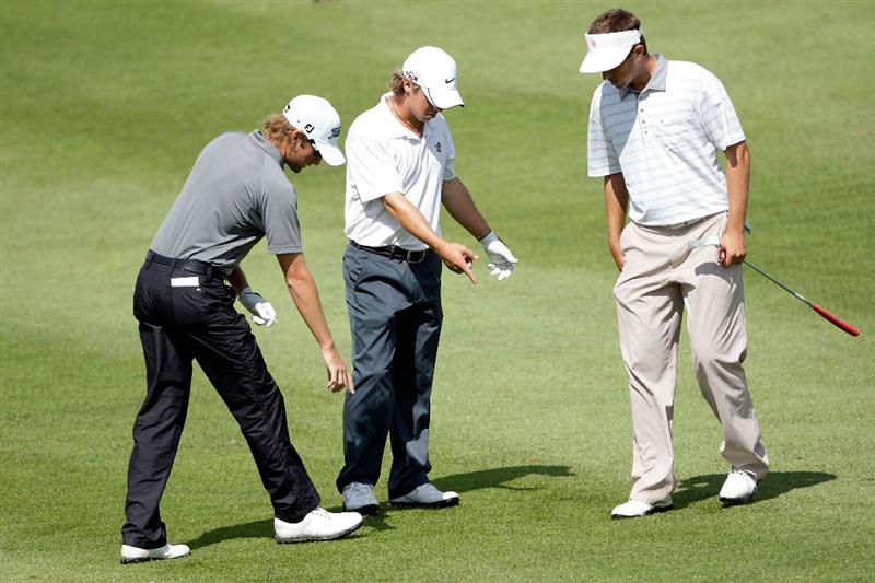 OVERLAND PARK, KS - AUGUST 20:  Michael Sim of Australia and Steve Friesen and Garrett Osborn of the U.S. discuss a lie on the sixth hole during the first round of the Nationwide Tour Christmas in October Classic on August 20, 2009 at Lions Gate Golf Club in Overland Park, Kansas.  (Photo by Jamie Squire/Getty Images)