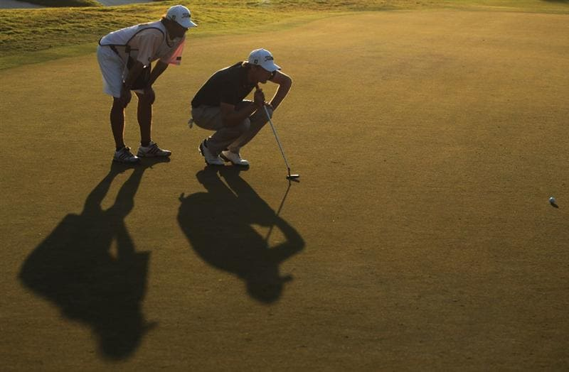 DORAL, FL - MARCH 13:  Nick Watney lines up his birdie putt on the 18th green with his caddie Chad Reynolds during the final round of the 2011 WGC- Cadillac Championship at the TPC Blue Monster at the Doral Golf Resort and Spa on March 13, 2011 in Doral, Florida.  (Photo by Scott Halleran/Getty Images)