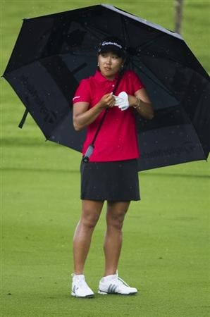 CHON BURI, THAILAND - FEBRUARY 20:  Lee Seon Hwa of South Korea shelters from the rain under her umbrella on the 5th hole during round three of the Honda PTT LPGA Thailand at Siam Country Club on February 20, 2010 in Chon Buri, Thailand.  (Photo by Victor Fraile/Getty Images)