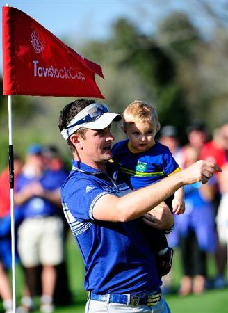 ORLANDO, FL - MARCH 23:  Justin Rose (L) of Great Britain carries his son Leo during the second day's play of the Tavistock Cup at Isleworth Golf and Country Club on March 23, 2010 in Orlando, Florida.  (Photo by Sam Greenwood/Getty Images)