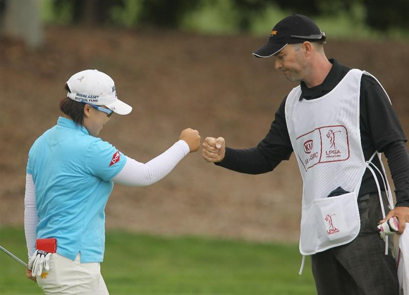 CITY OF INDUSTRY, CA - MARCH 27:  Jiyai Shin of South Korea celebrates a birdie putt on the 13th green with her caddie Shaun Clews during the final round of the Kia Classic on March 27, 2011 at the Industry Hills Golf Club in the City of Industry, California.  (Photo by Scott Halleran/Getty Images)