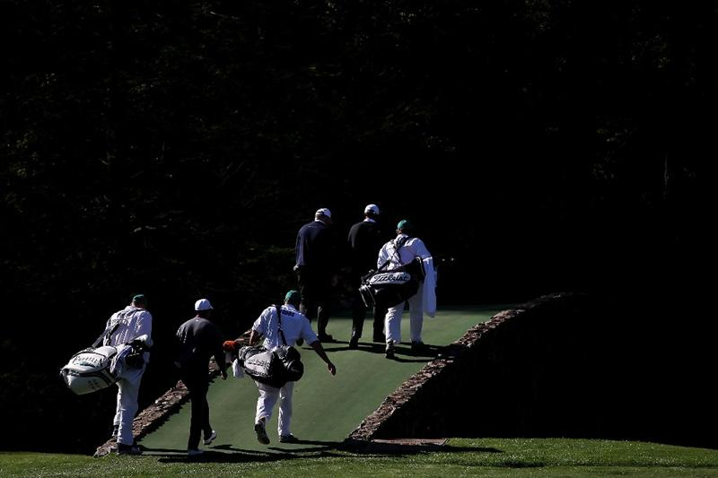 AUGUSTA, GA - APRIL 06:  The group of Tiger Woods, Mark O'Meara and Arjun Atwal of India walk across the Hogan Bridge with their caddies during a practice round prior to the 2011 Masters Tournament at Augusta National Golf Club on April 6, 2011 in Augusta, Georgia.  (Photo by Jamie Squire/Getty Images)