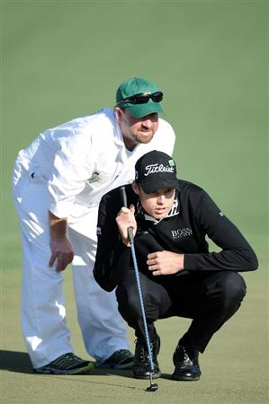 AUGUSTA, GA - APRIL 09:  Nick Watney lines up a putt with the help of his caddie Tim Goodell on the second hole during the second round of the 2010 Masters Tournament at Augusta National Golf Club on April 9, 2010 in Augusta, Georgia.  (Photo by Harry How/Getty Images)