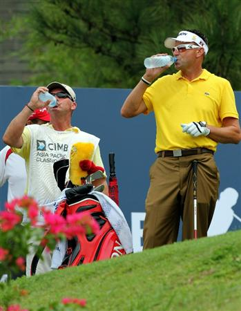 KUALA LUMPUR, MALAYSIA - OCTOBER 30: Robert Allenby of Australia and his caddie refreshes on the 9th hole during day three of the CIMB Asia Pacific Classic at The MINES Resort & Golf Club on October 30, 2010 in Kuala Lumpur, Malaysia. (Photo by Stanley Chou/Getty Images)