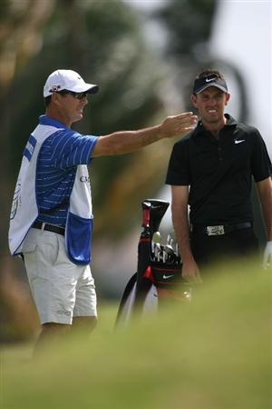 DORAL, FL - MARCH 14:  Charl Schwartzel of South Africa and his caddie discuss his shot on the second hole during the final round of the 2010 WGC-CA Championship at the TPC Blue Monster at Doral on March 14, 2010 in Doral, Florida.  (Photo by Marc Serota/Getty Images)