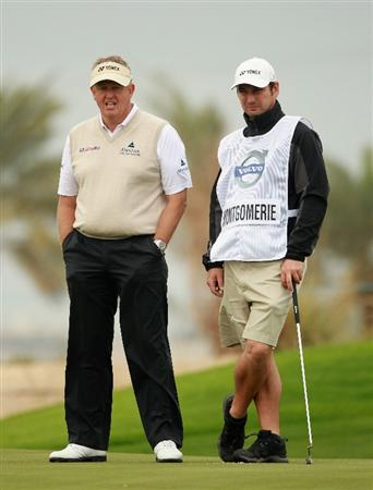 BAHRAIN, BAHRAIN - JANUARY 26:  Colin Montgomerie of Scotland walks with his caddie Jason Hempelman during the Pro Am prior to the start of the Volvo Golf Champions at The Royal Golf Club on January 26, 2011 in Bahrain, Bahrain.  (Photo by Andrew Redington/Getty Images)