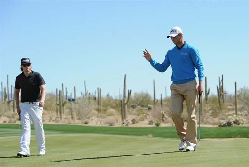 MARANA, AZ - FEBRUARY 25:  Martin Kaymer of Germany celebrates his putt on the 10th hole as he is watched by Hunter Mahan during the third round of the Accenture Match Play Championship at the Ritz-Carlton Golf Club on February 25, 2011 in Marana, Arizona.  (Photo by Stuart Franklin/Getty Images)