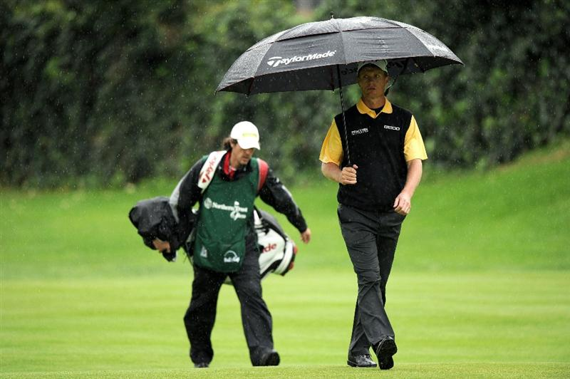 PACIFIC PALISADES, CA - FEBRUARY 18:  John Senden of Australia makes his way to the fairway with an umbrella on the 12th hole during the second round of the Northern Trust Open at the Riviera Country Club on February 18, 2011 in Pacific Palisades, California.  (Photo by Harry How/Getty Images)