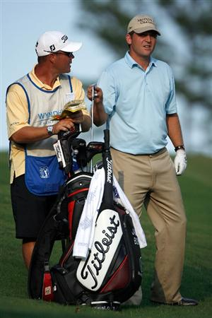 GREENSBORO, NC - AUGUST 23:  Jason Bohn pulls a club with his caddie on the 18th hole during the final round of the Wyndham Championship at Sedgefield Country Club on August 23, 2009 in Greensboro, North Carolina.  (Photo by Streeter Lecka/Getty Images)