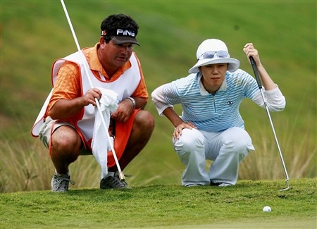 AVENTURA, FL - APRIL 26:  Young Kim and her caddie Steve Rosetti line up a birdie attempt on the ninth hole during the third round of the Stanford International Pro-Am at Fairmont Turnberry Isle Resort & Club on April 26, 2008 in Aventura, Florida.  (Photo by Doug Benc/Getty Images)