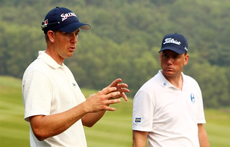 SHENZHEN, CHINA - NOVEMBER 27:  Robert Karlsson and Henrik Stenson of Sweden looks on during the Foursomes on the second day of the Omega Mission Hills World Cup on the Olazabal course on November 27, 2009 in Shenzhen, China.  (Photo by Ian Walton/Getty Images)
