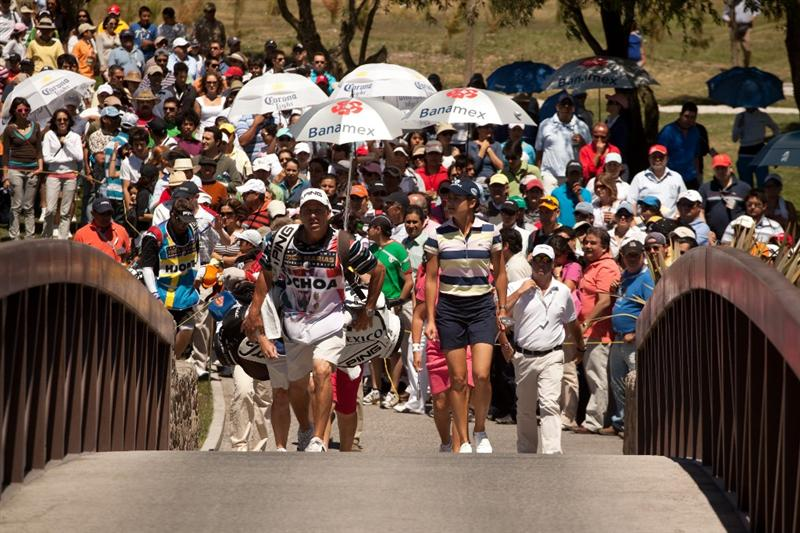 MORELIA, MEXICO - MAY 1: Lorena Ochoa of Mexico and caddie Greg Johnston walk across a bridge on the second hole during the third round of the Tres Marias Championship at the Tres Marias Country Club on May 1, 2010 in Morelia, Mexico. (Photo by Darren Carroll/Getty Images)