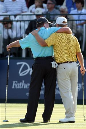 CHAMPIONS GATE, FL - DECEMBER 06:  Tom Kite of the USA puts his arms around his son David Kite on the 18th green during the first round of the Del Webb Father Son Challenge on the International Course at Champions Gate Golf Club on December 6, 2008 in Champions Gate, Florida.  (Photo by David Cannon/Getty Images)