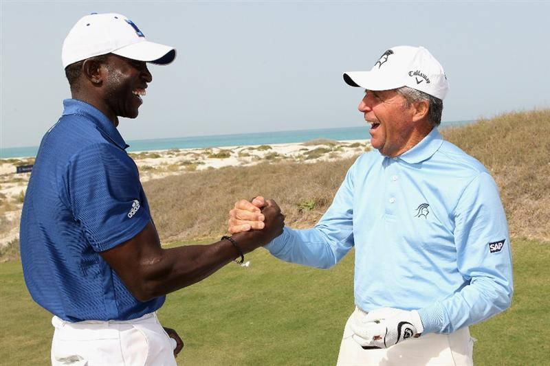 ABU DHABI, UNITED ARAB EMIRATES - FEBRUARY 06: Dwight Yorke and Academy Member Gary Player  shake hands during the Laureus Golf Challenge at the Saadiyat Beach Golf Club part of the 2011 Laureus World Sports Awards on February 6, 2011 in Abu Dhabi, United Arab Emirates.  (Photo by Ian Walton/Getty Images for Laureus)