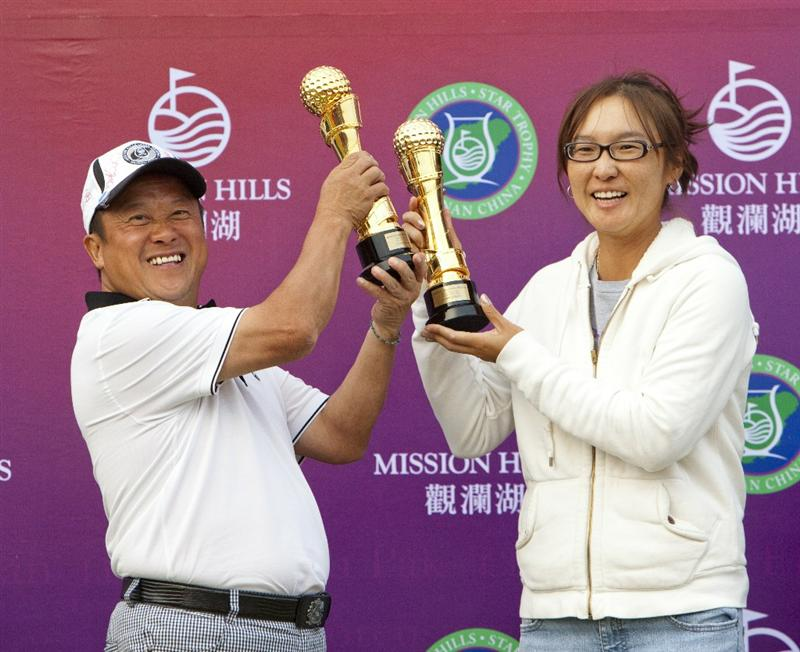 HAIKOU, CHINA - OCTOBER 31:  Hong Kong Actor Eric Tsang and golfer Candie Kung (R) of Taiwan pose after winning the 'Professional-Celebrity Champion Team' event during day five of the Mission Hills Start Trophy tournament at Mission Hills Resort on October 31, 2010 in Haikou, China. The Mission Hills Star Trophy is Asia's leading leisure liflestyle event which features Hollywood celebrities and international golf stars.  (Photo by Athit Perawongmetha/Getty Images for Mission Hills)