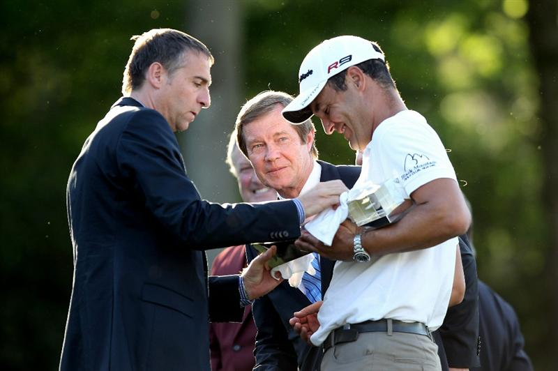 VIRGINIA WATER, ENGLAND - MAY 23:  Simon Khan of England receives the trophy following his victory, as European Chief executive George O'Grady looks on at the end of the final round of the BMW PGA Championship on the West Course at Wentworth on May 23, 2010 in Virginia Water, England.  (Photo by Ross Kinnaird/Getty Images)