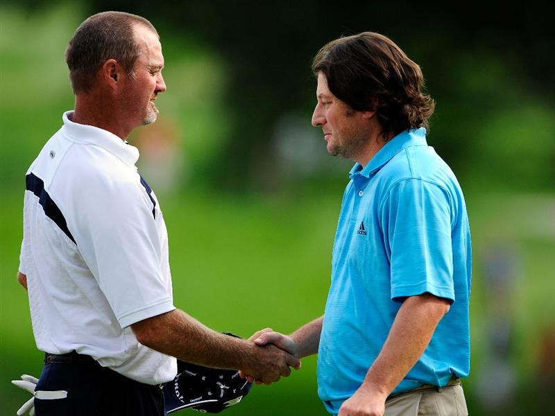 AKRON, OH - AUGUST 07:  Jerry Kelly (L) and Tim Clark of South Africa shake hands following the second round of the WGC-Bridgestone Invitational on the South Course at Firestone Country Club on August 7, 2009 in Akron, Ohio.  (Photo by Sam Greenwood/Getty Images)