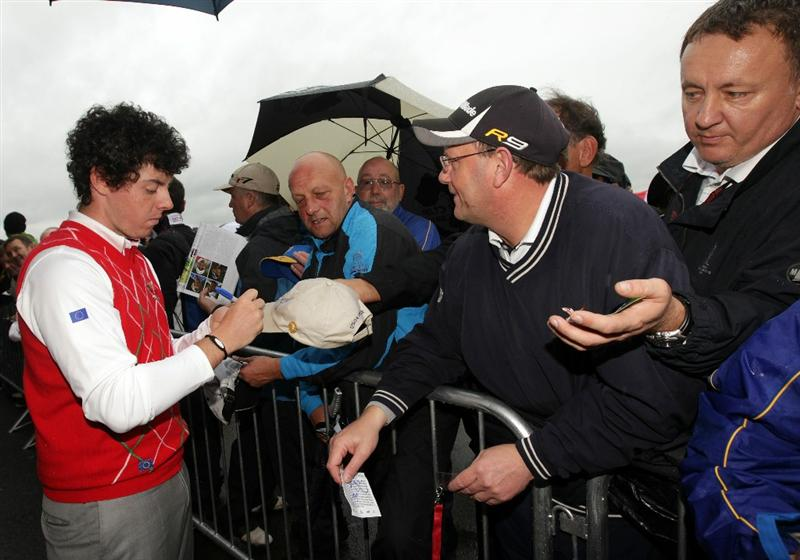 NEWPORT, WALES - OCTOBER 01:  Rory McIlroy of Europe signs autographs as rain falls and play is suspended during the Morning Fourball Matches during the 2010 Ryder Cup at the Celtic Manor Resort on October 1, 2010 in Newport, Wales.  (Photo by Andrew Redington/Getty Images)