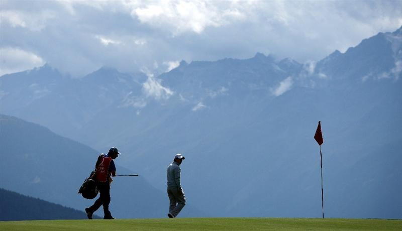CRANS, SWITZERLAND - SEPTEMBER 03:  Rory McIlroy of Northern Ireland walks across the green with his caddie JP Fitzgerald on the seventh hole during the first round of The Omega European Masters at Crans-Sur-Sierre Golf Club on September 3, 2009 in Crans Montana, Switzerland.  (Photo by Andrew Redington/Getty Images)