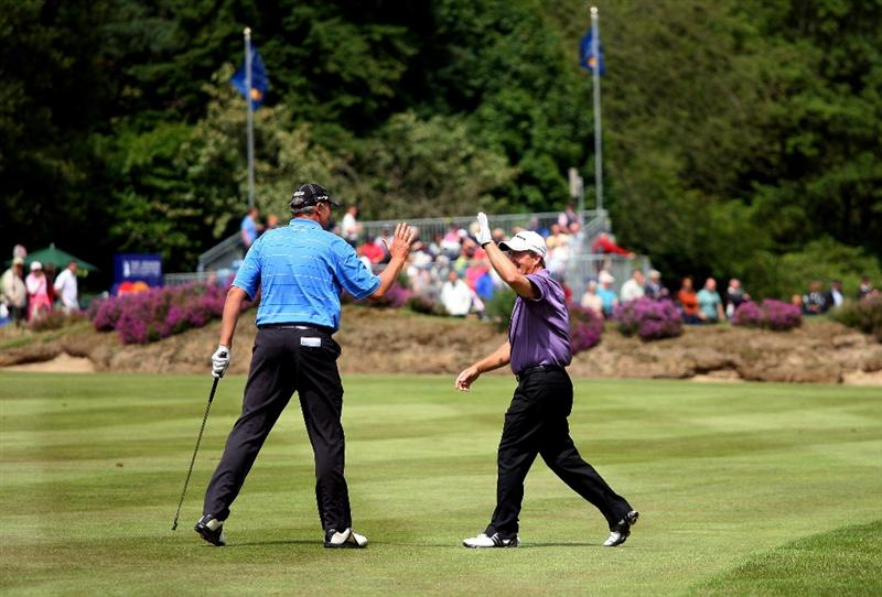 SUNNINGDALE, ENGLAND - JULY 24:  Fred Funk of the USA (right) is congratulated by playing patner Mike Harwood of Australia after holing his second shot for an eagle on the 18th hole during the second round of The Senior Open Championship presented by MasterCard held on the Old Course at Sunningdale Golf Club on July 24, 2009 in Sunningdale, England.  (Photo by Andrew Redington/Getty Images)