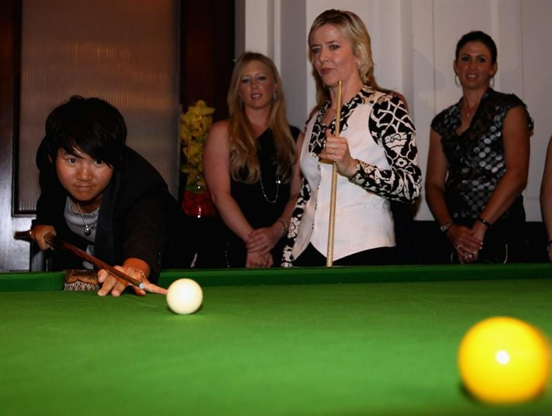 SINGAPORE - FEBRUARY 23:  Yani Tseng of Taiwan receives a snooker lesson from Allison Fisher as Morgan Pressel and Nicole Castrale (both of the USA) look on during the Welcome Reception prior to the start of the HSBC Women's Champions at the Tanah Merah Country Club on February 23, 2011 in Singapore.  (Photo by Andrew Redington/Getty Images)
