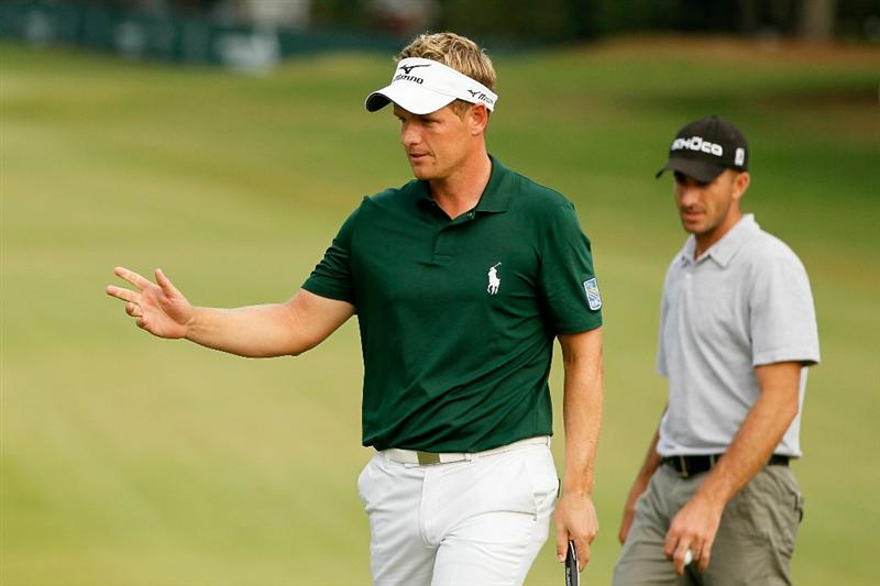 ATLANTA - SEPTEMBER 24:  Luke Donald of England reacts after his birdie putt on the 16th green as Geoff Ogilvy of Australia walks up for his birdie putt during the second round of THE TOUR Championship presented by Coca-Cola at East Lake Golf Club on September 24, 2010 in Atlanta, Georgia.  (Photo by Kevin C. Cox/Getty Images)