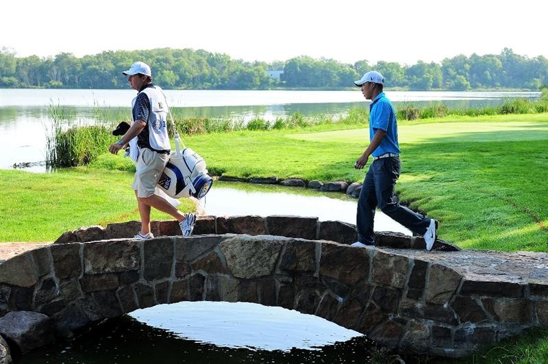 CHASKA, MN - AUGUST 14:  Anthony Kim waits with his caddie Eric Larson across a birdie on the 16th hole during the second round of the 91st PGA Championship at Hazeltine National Golf Club on August 14, 2009 in Chaska, Minnesota.  (Photo by Stuart Franklin/Getty Images)