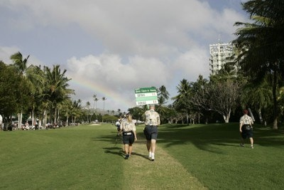 With a rainbow in the background, volunteers carry a the scorecard of Paul Goydos and Luke Donald during the third round of the Sony Open in Hawaii held at Waialae Country Club in Honolulu, Hawaii, on January 13, 2007. Photo by Marco Garcia/WireImage.com