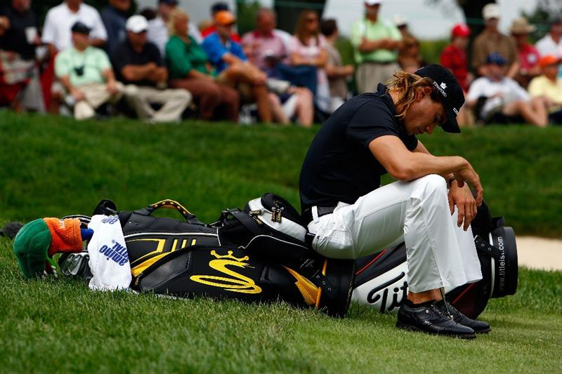 ST. LOUIS - SEPTEMBER 06:  Camilo Villegas of Columbia sits on his bag while his playing partners putt out on the 9th hole during the second round of the BMW Championship on September 6, 2008 at Bellerive Country Club in St. Louis, Missouri.  (Photo by Jamie Squire/Getty Images)