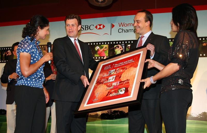 SINGAPORE - MARCH 04:  Lorena Ochoa of Mexica and Se Ri Pak of South Korea present a gift to Guy Harvey-Samuel, CEC Singapore and Giles Morgan Group Hrad of Sponsorship of HSBC at the 'Welcolm Reception' prior to the HSBC Women's Champions at the Tanah Merah Country Club on March 4, 2009 in Singapore.  (Photo by Ross Kinnaird/Getty Images)